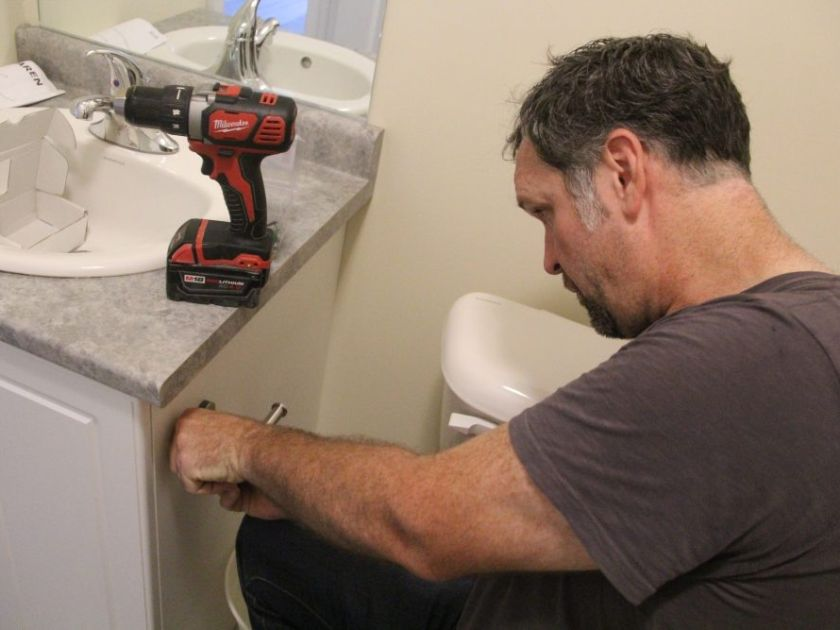 Graham Cubitt preparing an apartment bathroom at Woodfield Gate prior to opening