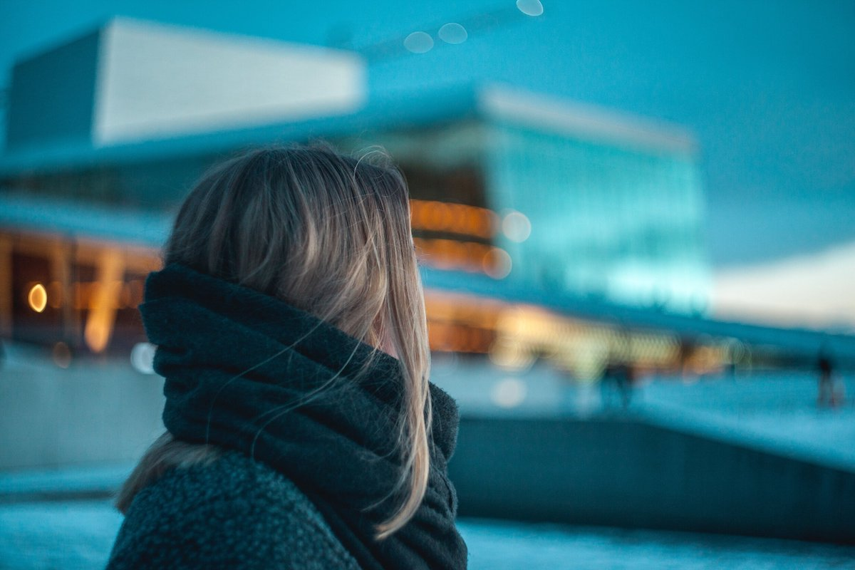 Woman looking at apartment building