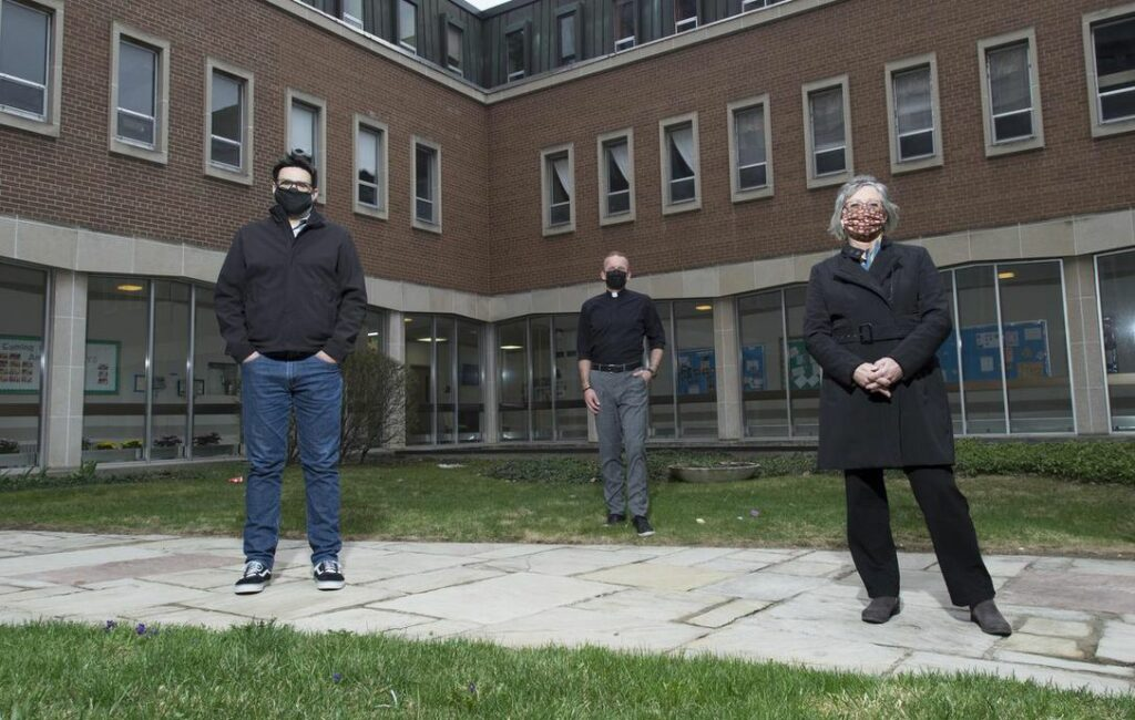 Three people (including Mark Willcock Left) in the courtyard in front of St Peter's Church, Kitchener